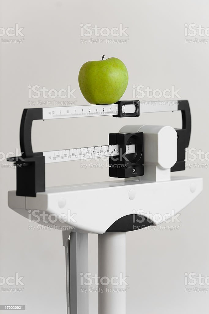 Apple on medical weight scale royalty-free stock photo