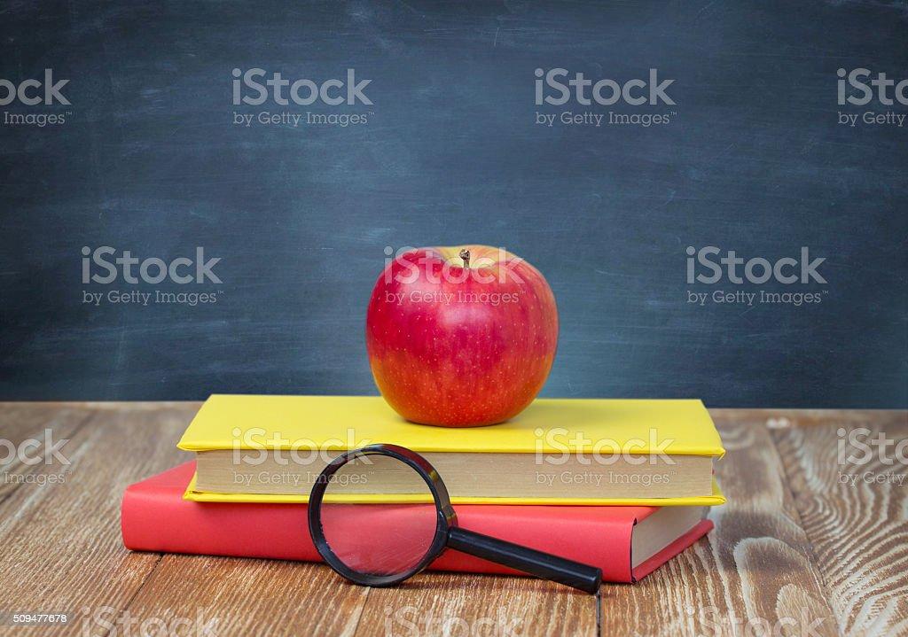 Apple on stack books blackboard background empty space. stock photo