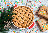 Apple pie, christmas gifts and decorations on light background