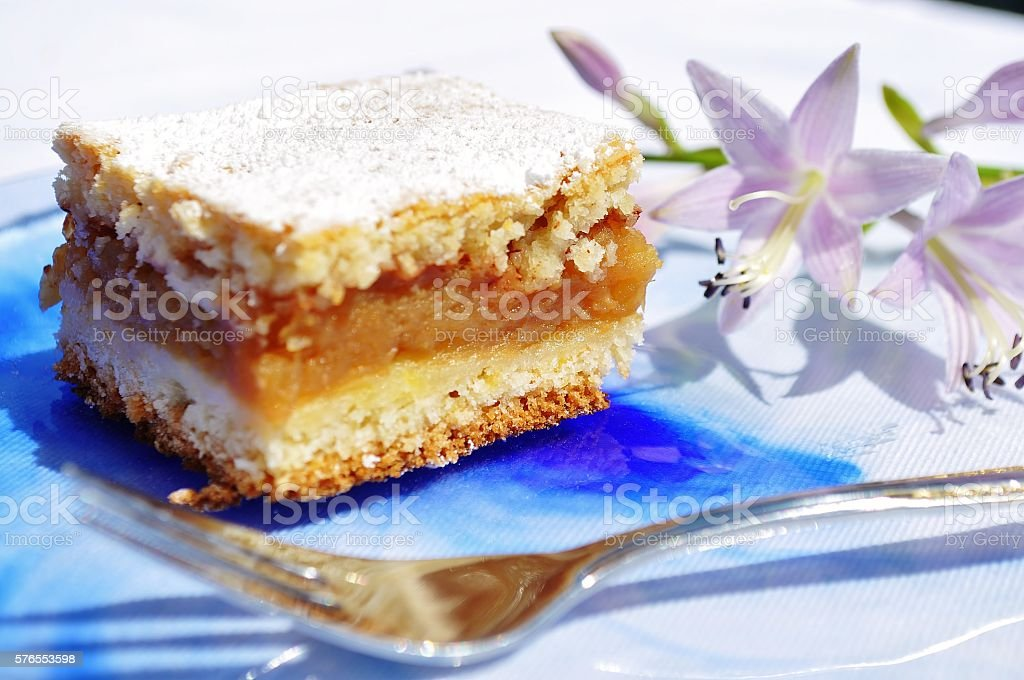 Apple pie, fork and violet flower on plate with bluesmudges. stock photo
