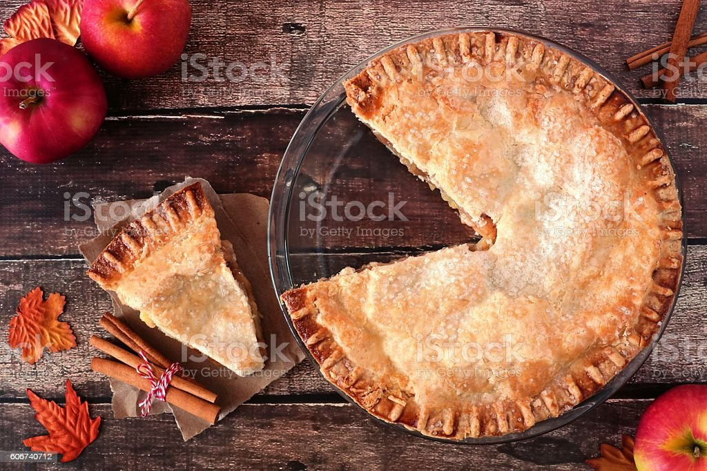 Apple pie, overhead scene with cut slice on rustic wood stock photo