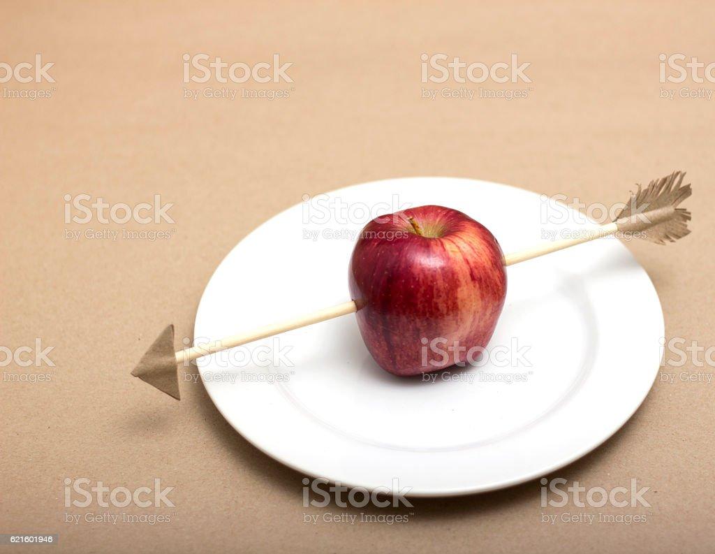 Apple pierced by toy arrow stock photo