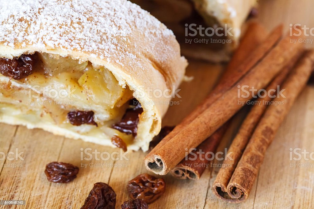 Apple strudel with icing sugar, cinnamon sticks, wooden background stock photo