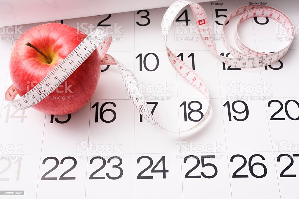 Apple with a measuring tape on the calendar stock photo