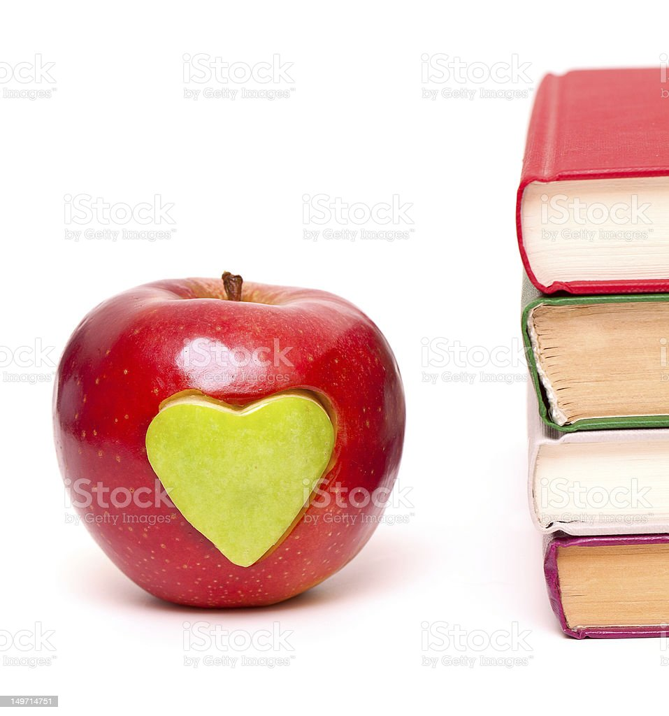 apple with green heart and stack of books stock photo