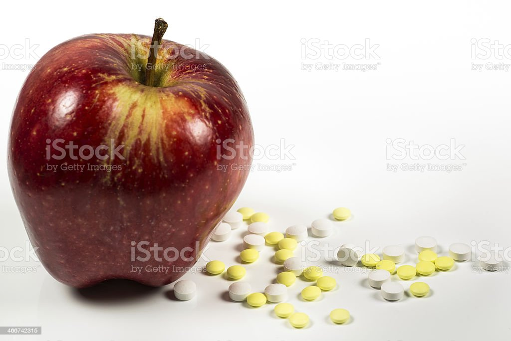 apple with lots of medical pills on the side stock photo