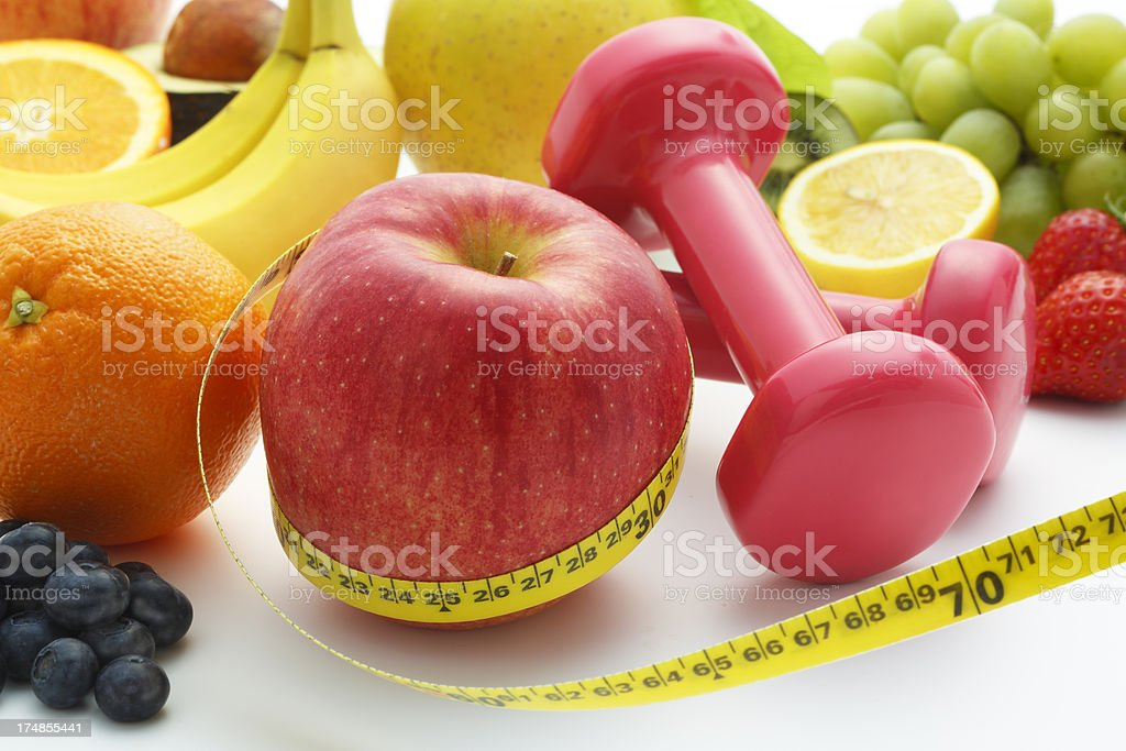 Apple wrapped in tape measure next to fruit and hand weights royalty-free stock photo