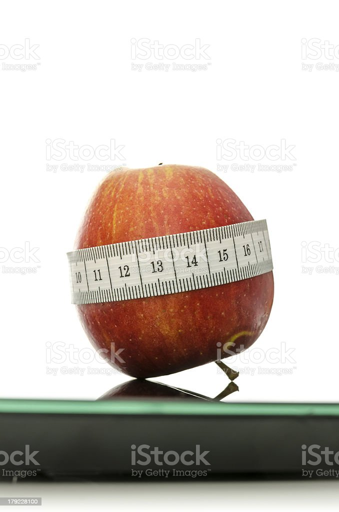 Apple wrapped with measuring tape on a scale royalty-free stock photo
