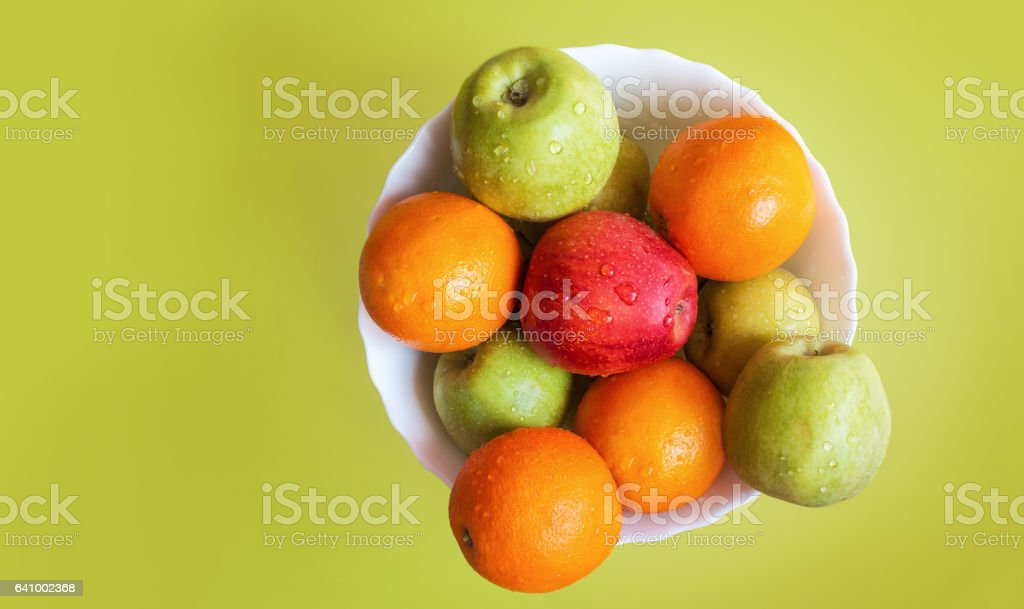apples and orange on white dish, olive background top view stock photo