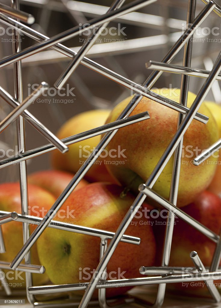 Apples behind silver metal rods royalty-free stock photo
