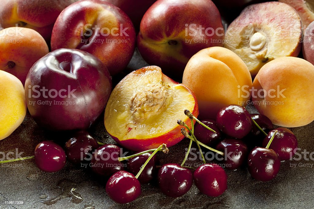 Apples cherries and peaches on a wooden table stock photo