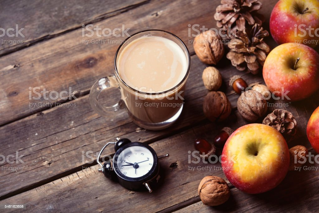 apples, fir-cones, cup of coffee, clock and nuts stock photo