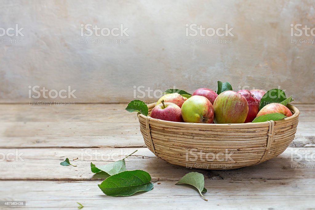 apples in a basket on an rustic wooden table stock photo