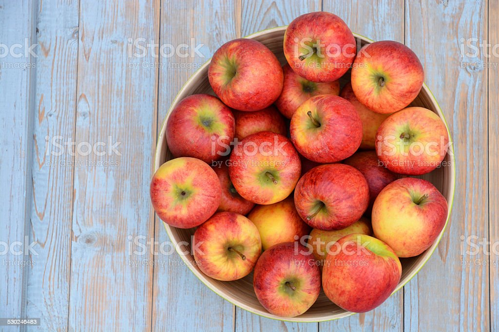 apples in a green fruit bowl on wooden background stock photo