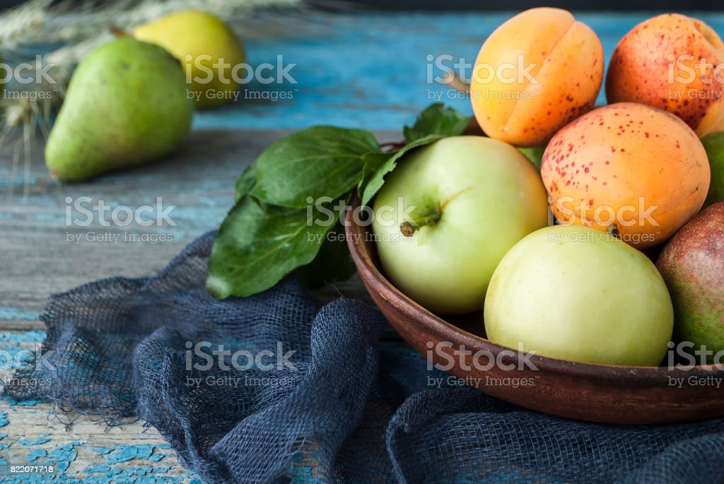 Apples, pears and apricots in a plate on a wooden table stock photo