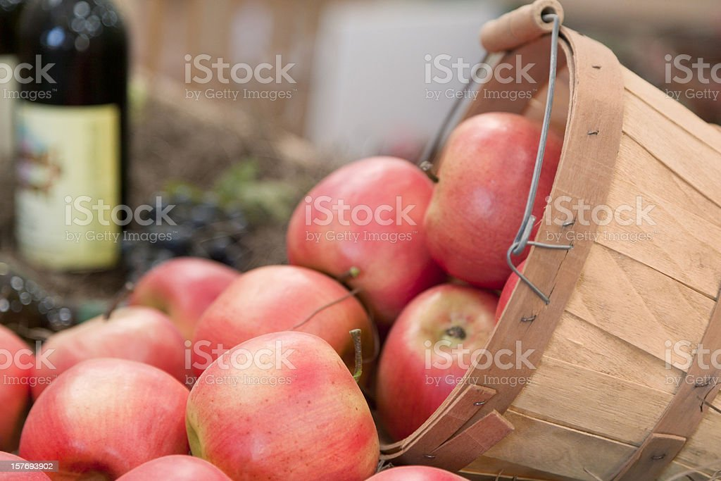 Apples Spilling Out of Basket, Wine Bottle in Background royalty-free stock photo