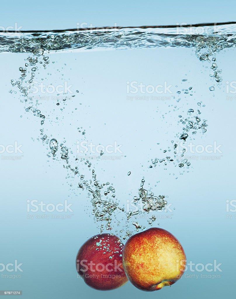Apples splashing in water royalty-free stock photo
