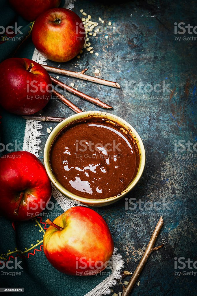 Apples, sticks and hot liquid chocolate on rustic background stock photo