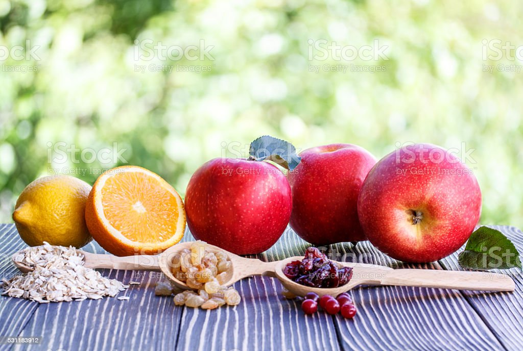 Apples,orange, nuts,cranberry, lemon, muesli and raisins stock photo