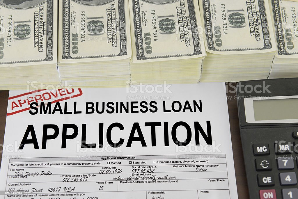 Application for a small business loan and US dollar bills stock photo