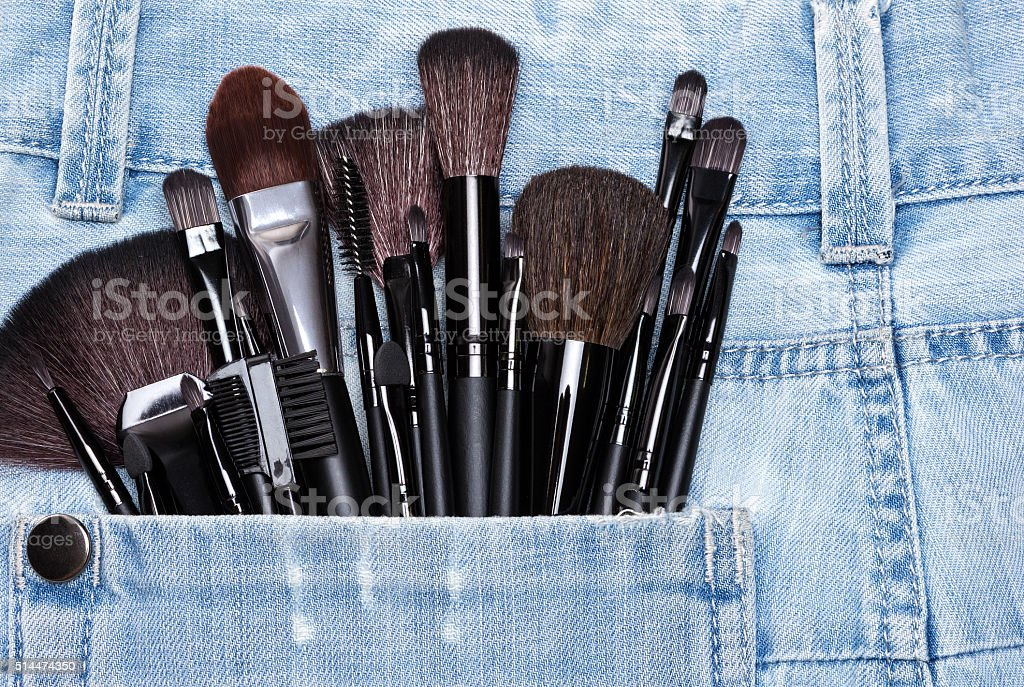 Applicators and makeup brushes in jeans pocket stock photo