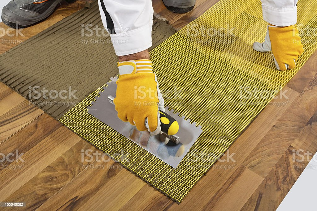applies tile adhesive on wooden floor with reinforce fiber mesh stock photo