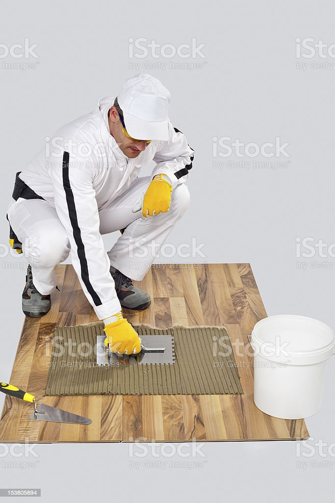 Appling Tile Adhesive with Notched Trowel on a old wood stock photo