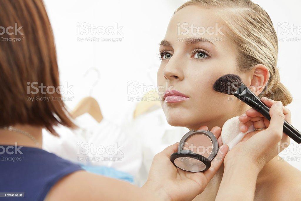 Applying blush on cheeks royalty-free stock photo