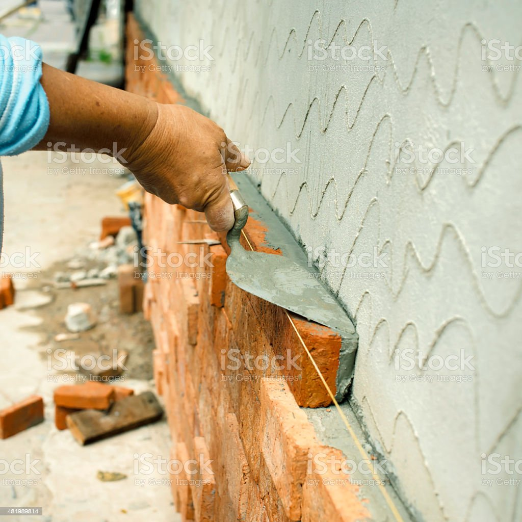 Applying construction trowel with brick wall stock photo