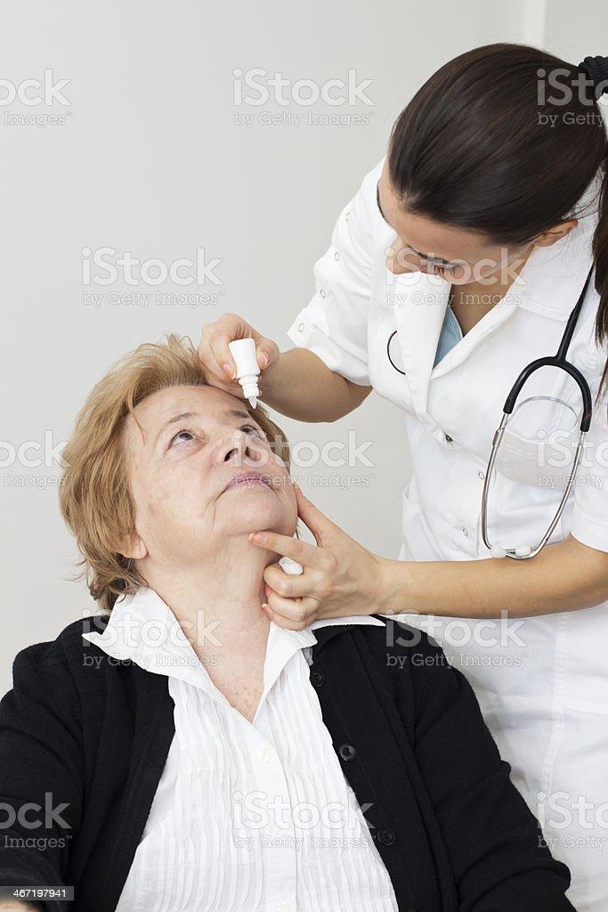 Applying eye drops stock photo