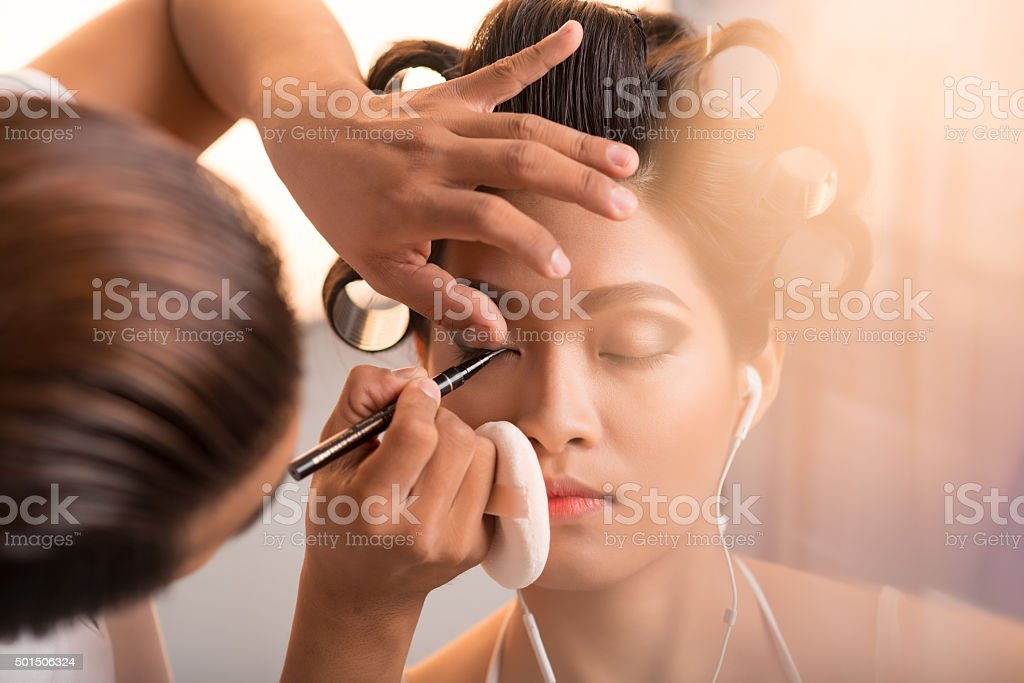 Applying eyeliner stock photo