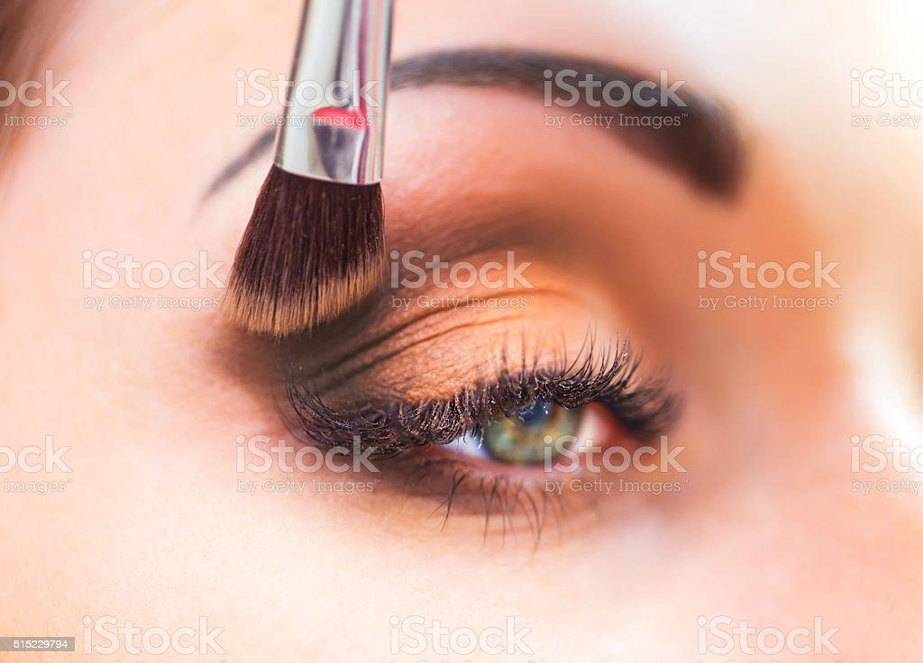 Applying eyeshadow on eyelid. stock photo
