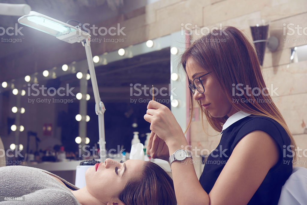 applying false eyelashes stock photo
