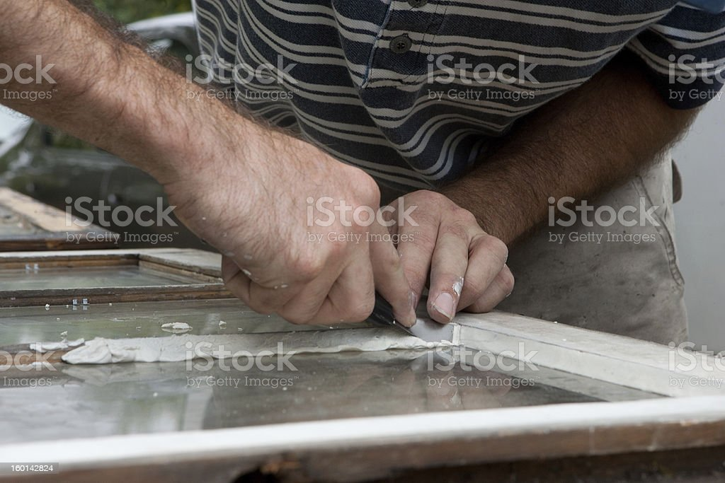 Applying glazing to old window. royalty-free stock photo