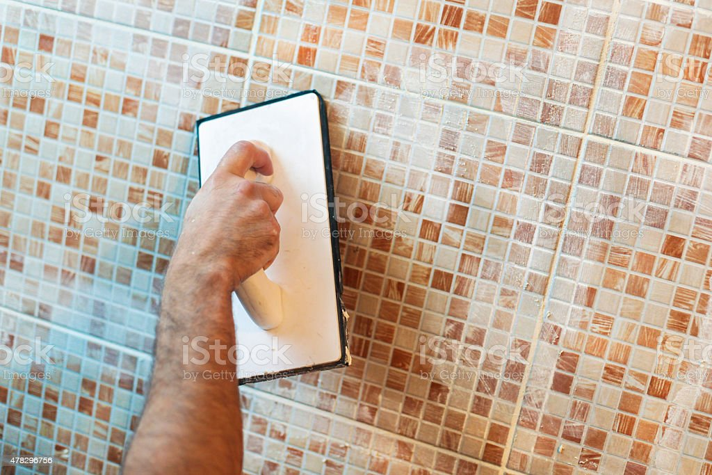 Applying grout on ceramic tiles stock photo