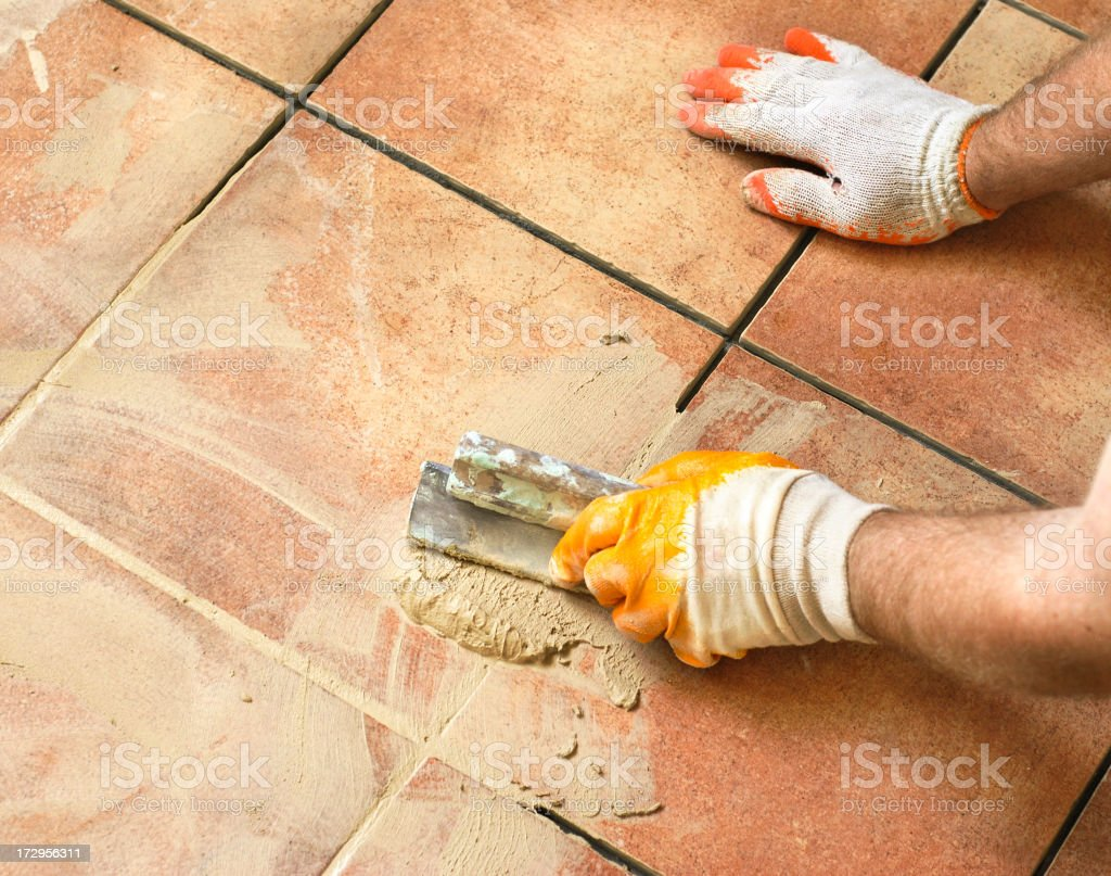 Applying grout stock photo