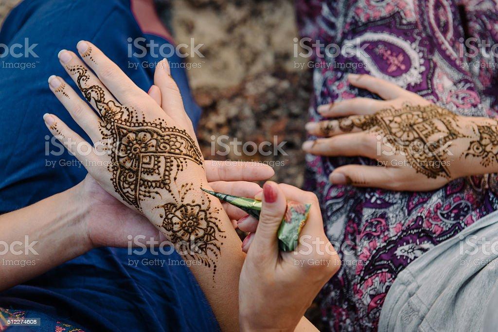 applying henna tattoo on women hands.  top view stock photo