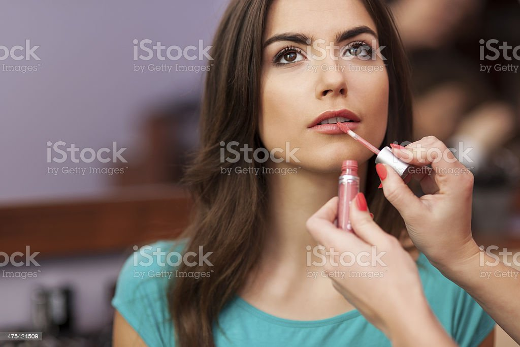 Applying lip-gloss to the lips of beautiful woman stock photo