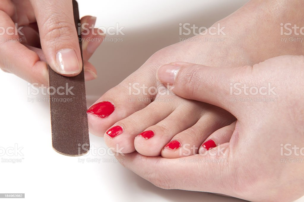Applying Nail File on Toe stock photo