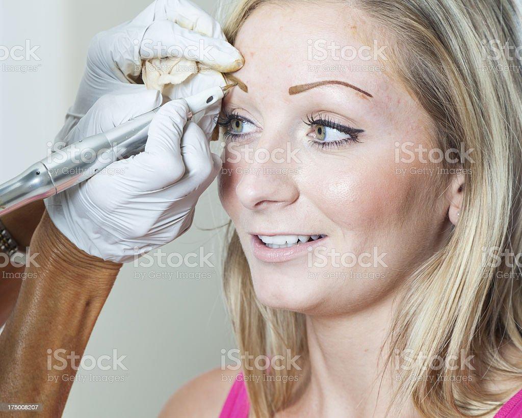 Applying Permanent Makeup royalty-free stock photo