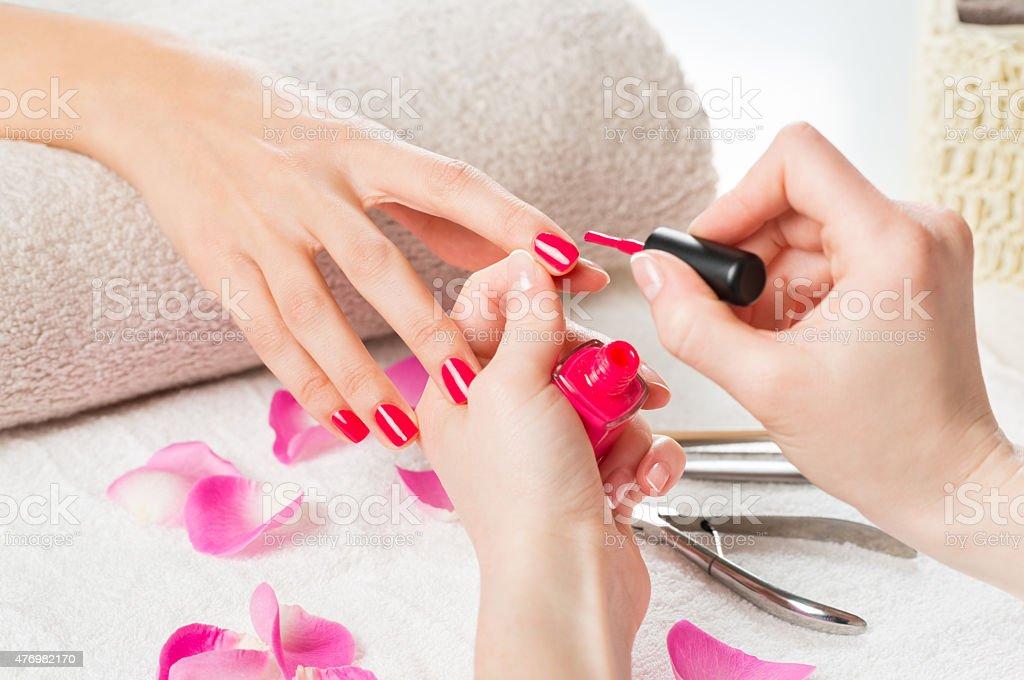 Applying pink nail polish stock photo