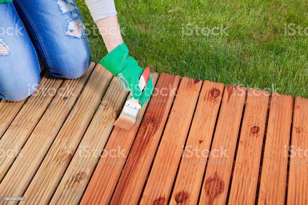 Applying protective varnish on a patio wooden floor stock photo