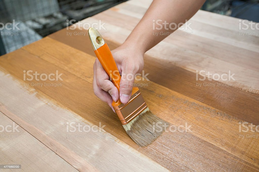 Applying protective varnish on a wooden furniture stock photo