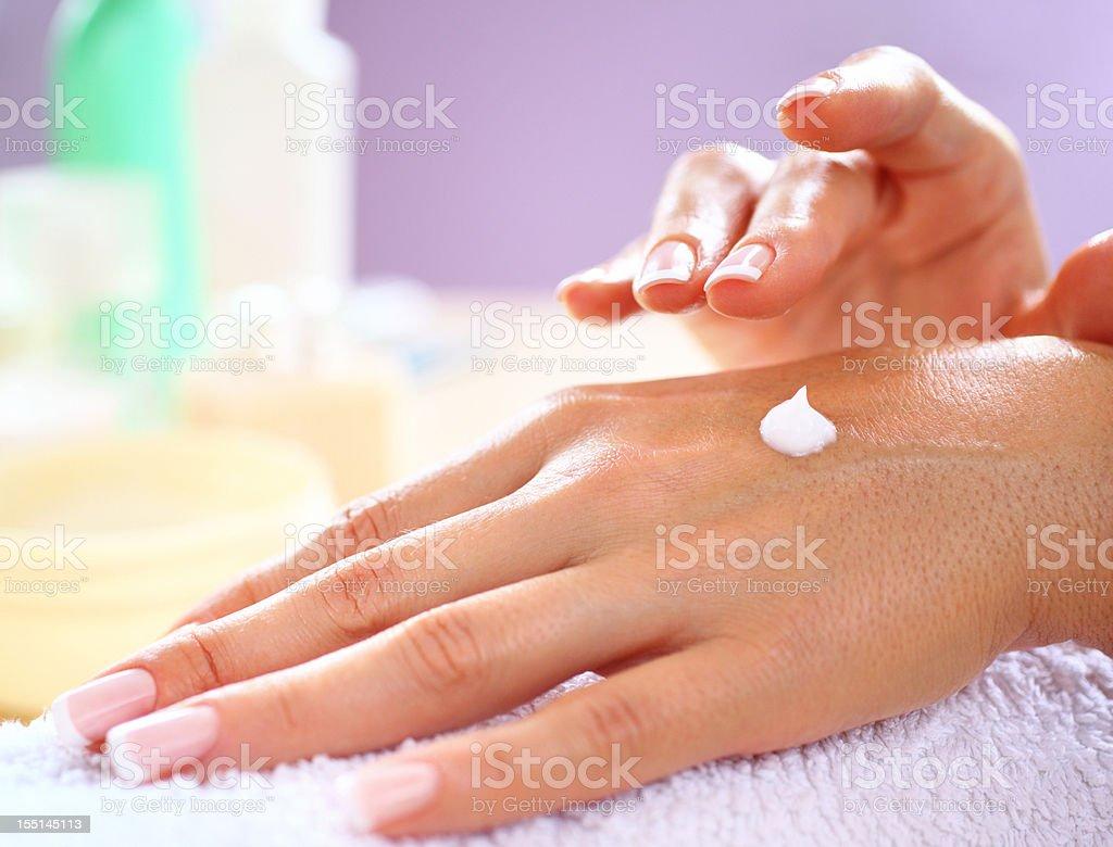 Applying skin moisturizer royalty-free stock photo