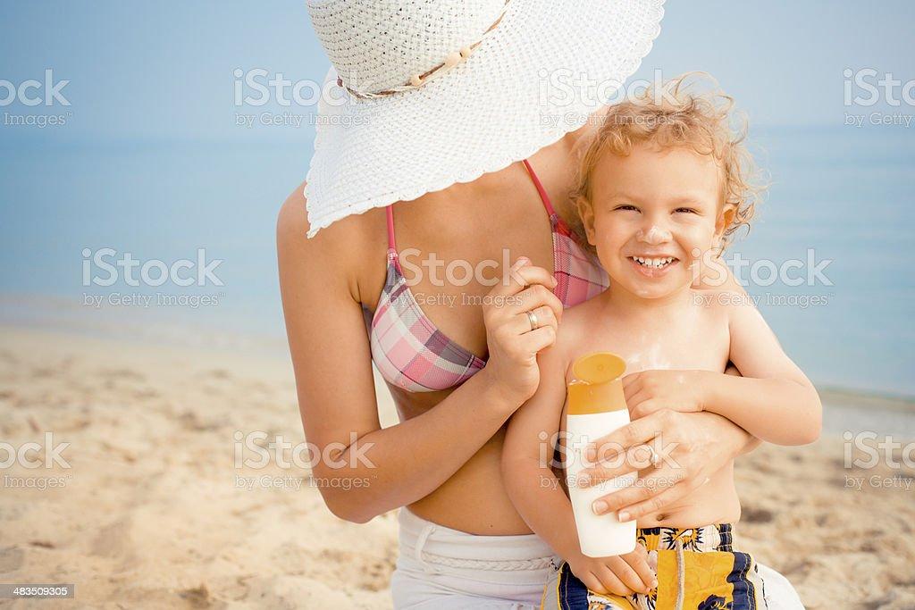 Applying sunscreen at the beach stock photo