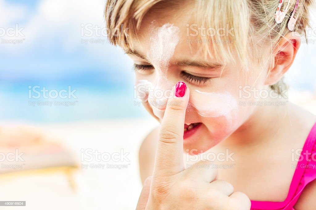 Applying sunscreen to child's face stock photo