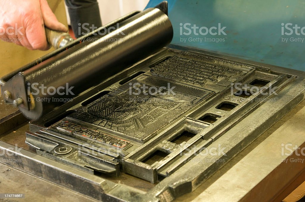 Applying the ink to a printing block with a roller stock photo