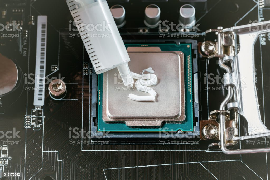 Applying thermal paste during CPU installation close up in the motherboard stock photo