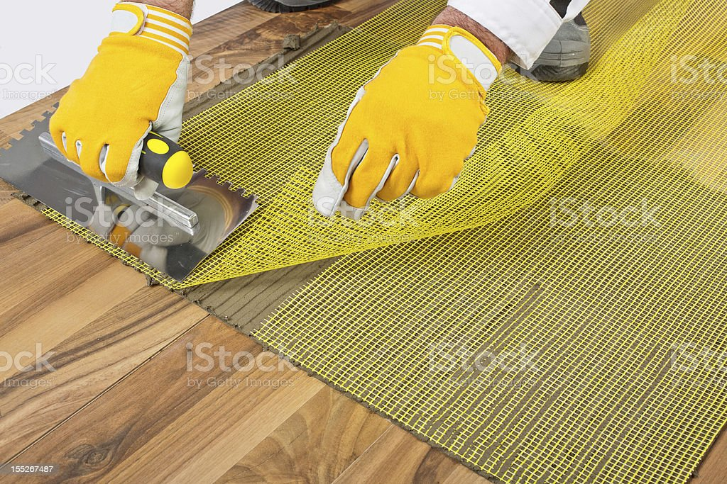 applying tile adhesive with reinforcement mesh on wooden floor stock photo