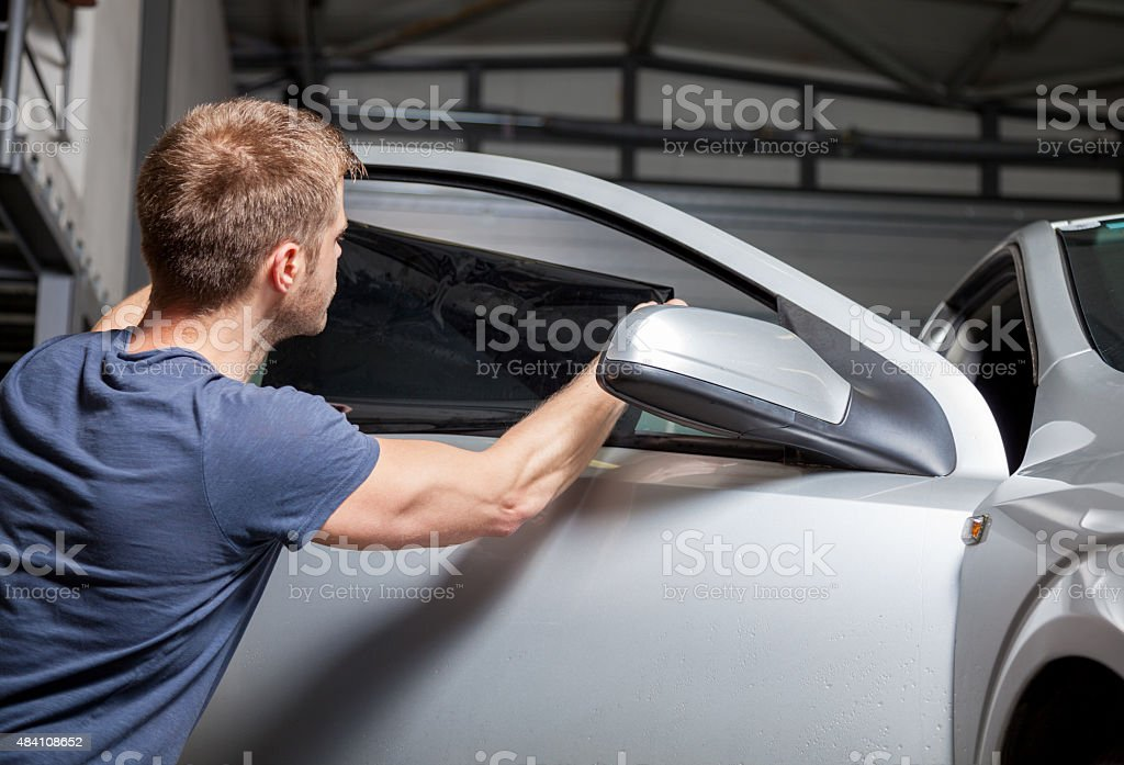 Applying tinting foil on a car window stock photo